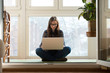 Woman sitting lotus pose laptop floor home