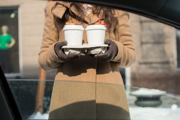 Woman holding coffee outdoors car window