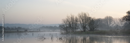 Panorama landscape of lake in mist with sun glow at sunrise - 68928072