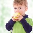 Kind beißt in einen grünen Apfel