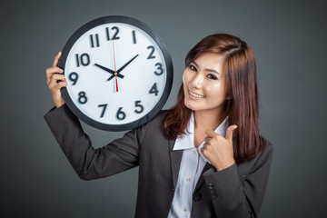 Asian businesswoman hold a clock thumbs up and smile