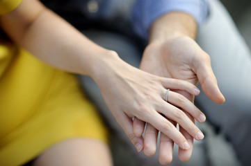 Man holding woman's hand with engagement ring