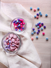 Different beads in glass bowls on fabric on table