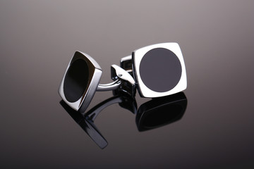 Pair of cuff links on dark grey background