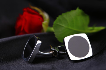 Pair of cuff links with red rose on black silk fabric