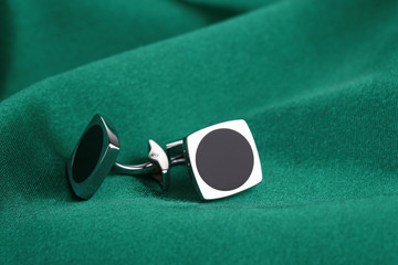 Pair of cuff links on green silk fabric  background