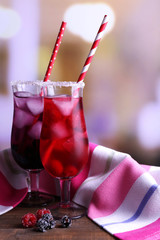 Glasses of cold berry cocktail and napkin on wooden table