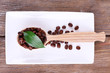Wooden spoon of coffee beans on tray on wooden background