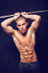 Fit shirtless young man in gym