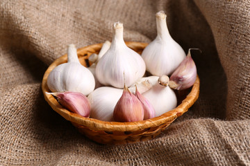 Fresh garlic in wicker basket on sackcloth background