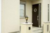 住まいの玄関イメージ(クリームのサイディングとモダンな丸い窓)