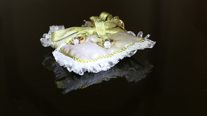 two wedding rings with diamonds lying on a wedding pillow with a
