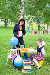 Beautiful asian woman teacher talking reading book to shoolgirl