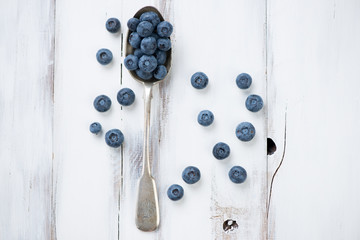 Ripe blueberries in a spoon over white wooden background