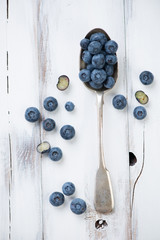 Spoon with ripe blueberries, white wooden surface, above view