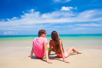 happy young couple sitting at tropical beach