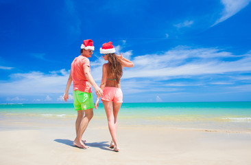 back view of young couple in santa hats having fun at tropical