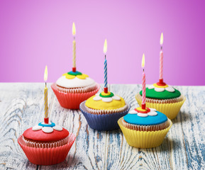Birthday cupcakes with burning candles on the background purple