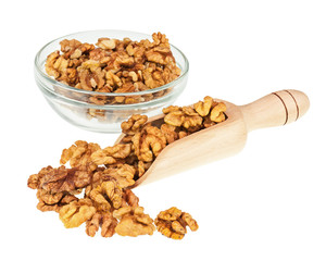 Handful of walnuts in scoop and glass bowl isolated on white.