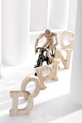 Doping Buchstaben und Holzfigur auf Fahrrad