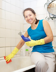 Smiling  mature woman cleans bathtub