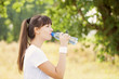 Runner woman drinking water after jogging