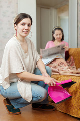 Clean up woman, while mature mother reads newspaper