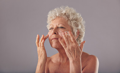 Beautiful old woman applying moisturizer on her face