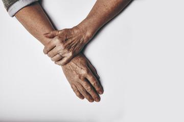 Elderly woman's hands on grey background