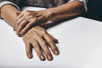 Old female hands on a table
