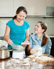 women cooking  dumplings with electric steamer