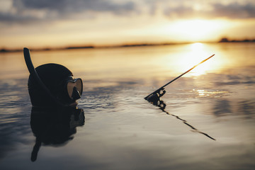 Spearfishing diver submerged in water during evening
