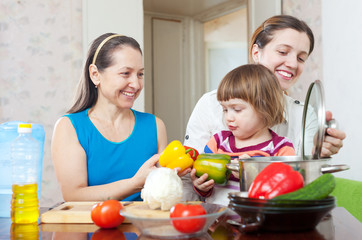 women of three generations cook  in the kitchen
