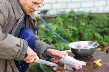man cut up fish for cooking