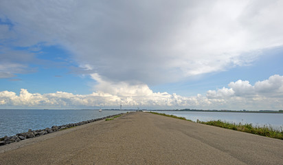 Clouds over a dike in a lake