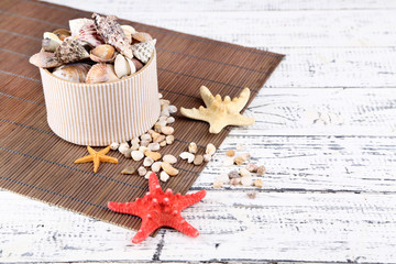 White box full of sea gifts on white wooden background