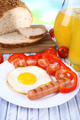 Scrambled egg with bread, vegetable and sausage served in plate