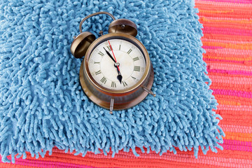 Metal clock on a blue pillow on red background