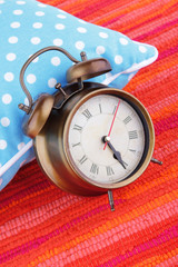 Metal clock on a blue polka dot pillow on red background