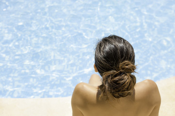 young woman sitting on the pool edge