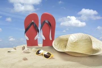Escena de playa con chanclas, sombrero y gafas de sol