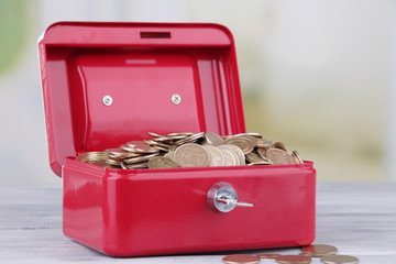 Rectangular red open suitcase with Ukrainian coins