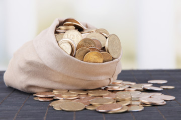 Fabric bag full of Ukrainian coins on wooden background
