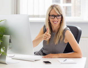 Young smiling businesswoman showing thumbs up gesture