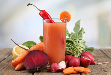 Fresh carrot juice with vegetables on wooden table