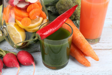 Jar of cut vegetables and glass of fresh vegetable juice with