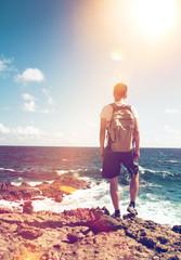 Mann steht auf einem Felsen und blickt auf das Meer