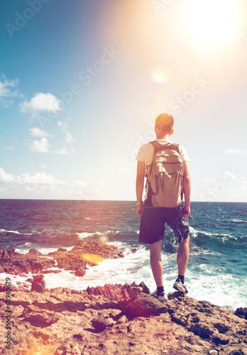 canvas print picture Mann steht auf einem Felsen und blickt auf das Meer