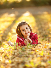 Little girl portrait in autumn sunny park