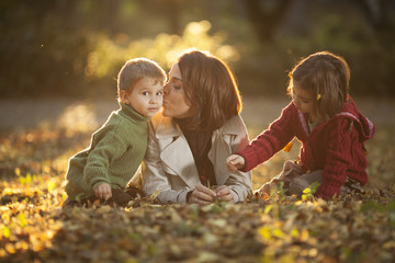 Mother enjoying with her children in autumn park.